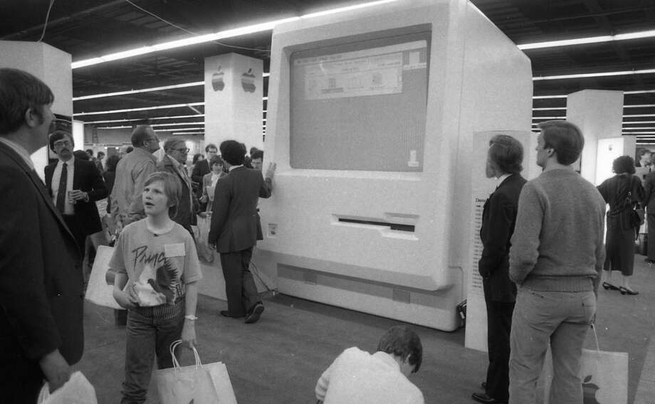 MACWORLD: Behold photos from the first MacWorld, a comparatively tiny event at Brooks Hall in San Francisco. Proof that this was 1985: The giant Mac and the kid in the Prince ''Purple Rain'' shirt. Photo: Steve Ringman, The Chronicle