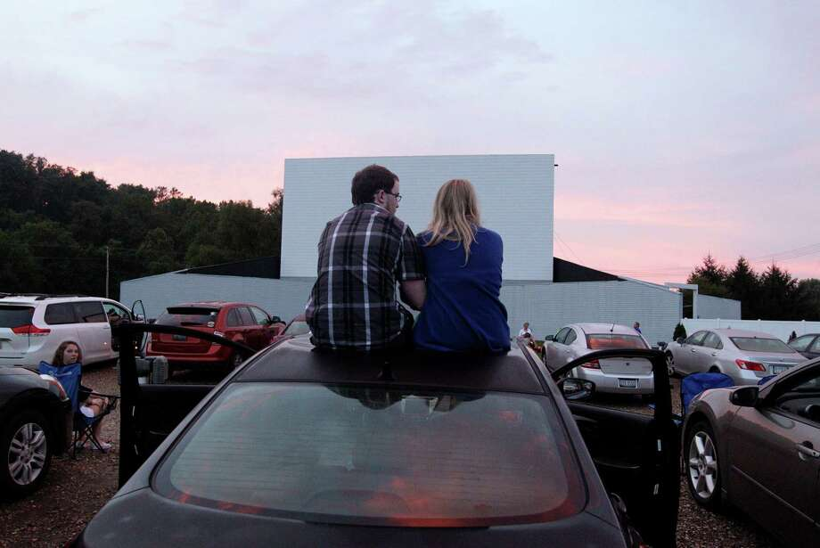 In this July 20, 2013 photo, Alex Lockhart, left, and Mikayla Green, both of Newark, watch the sunset while waiting for the movie to start at the Skyview drive-in theater in Lancaster, Ohio. The Skyview was the first drive-in theater in Ohio to convert to a digital projector. The latest threat to the existence of drive-in theaters is the conversion from 35mm film to digital prints and the expense involved in converting projectors to the new format. Photo: Jay LaPrete