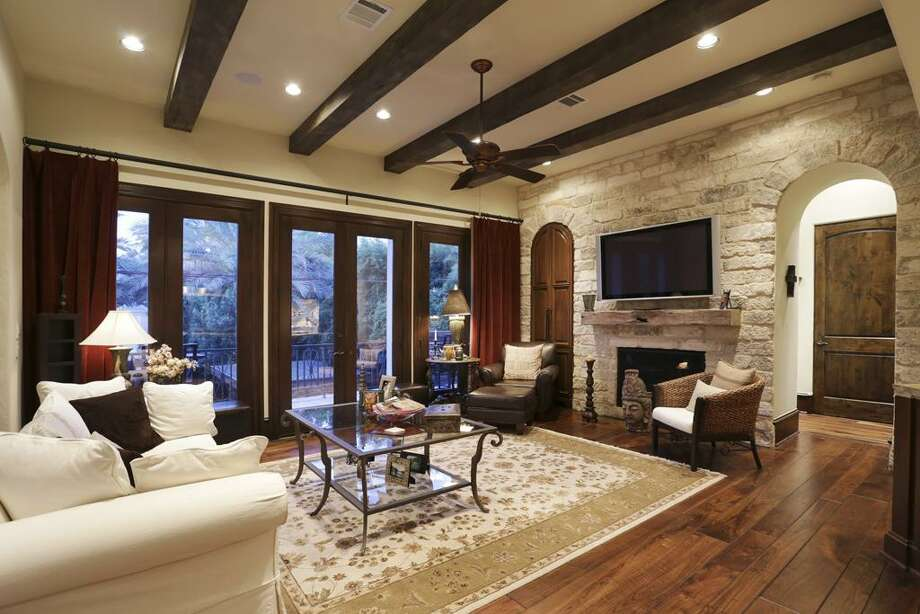 Living room - exposed beams, stone fireplace, mahogany doors to balcony overlooking pool.