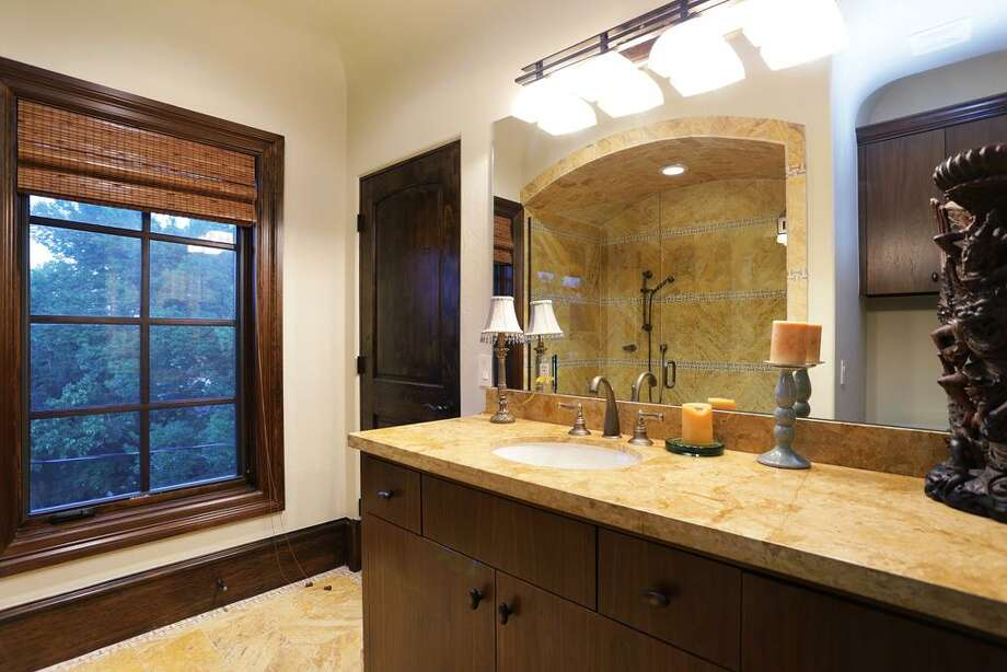 Full bath with marble counter top, floor, and shower.