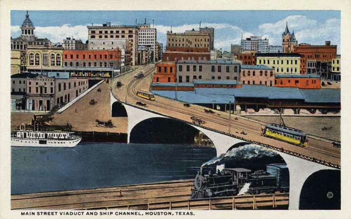 HOUSTON - 1909: Vintage postcard showing the Main Street Viaduct and Ship Channel Streetcars travel the viaduct over the channel as a train travels the tracks under the viaduct A ship is in the channel and the city is visible across the channel. (Photo by Lake County Museum/Getty Images)