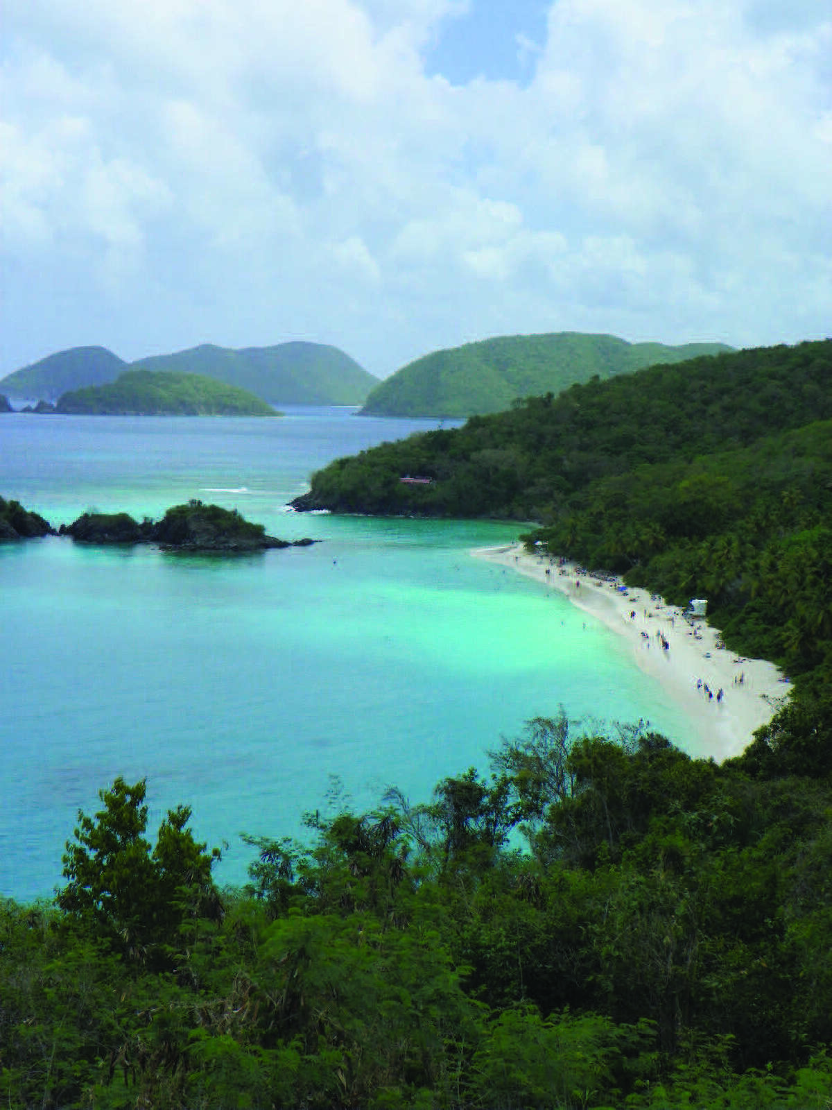 The turquoise water and white sandy beach of Trunk Bay can be enjoyed up close or from this overlook. Trunk Bay has one of the most popular beaches on the island of St. John. Below: Tropical plants surround the door to the Calypso Del Sol rental home in St. John.
