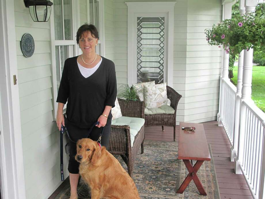 Joan Gallagher and her Golden Retriever on the porch of 216 Main Street, New Canaan, Conn. Photo: Tyler Woods