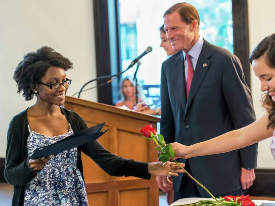 """Donna Joseph gets a rose from Andrea Lopez Salazar at the """"Let's Get Ready"""" Summer program graduation ceremony. The ceremony was held at the Old Town Hall in Stamford, CT on Wednesday, August 14th, 2013. The ceremony included U.S. Senator, Richard Blumenthal, Executive Director of LetâÄôs Get Ready, Lauri Novick, and Economic Development Director for the City of Stamford, Laure Aubuchon. Photo: Mark Conrad / Stamford Advocate Freelance"""