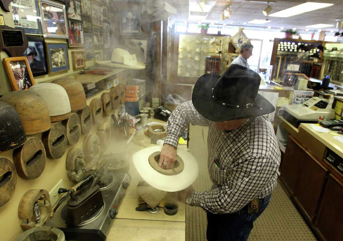 Gary Cohen, owner of the Hat Store, steams a hat.