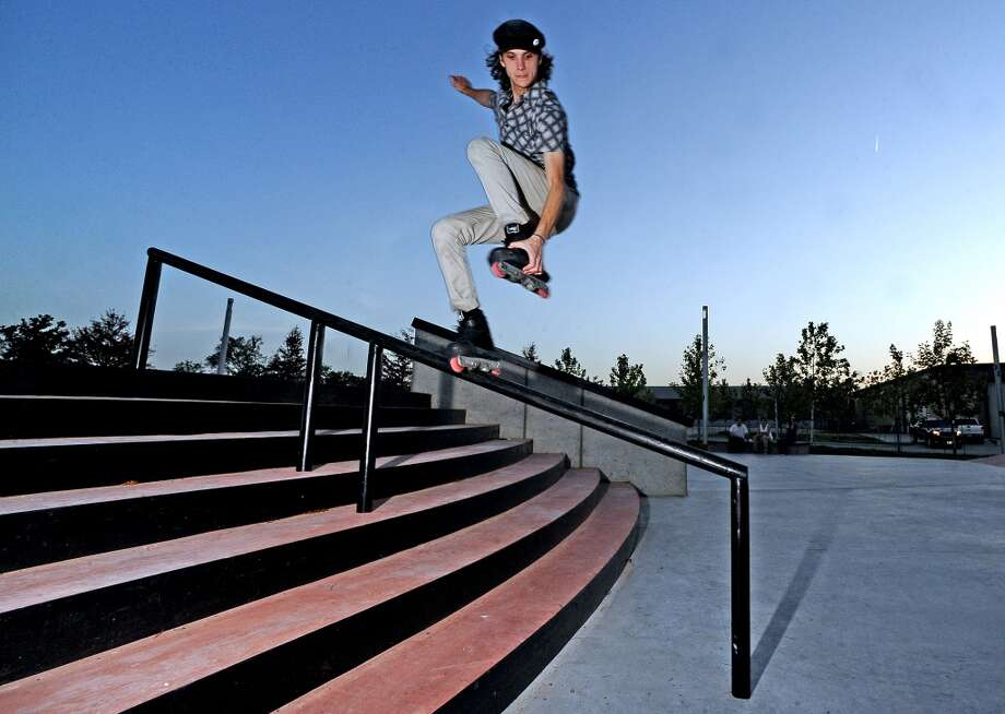 Isaac Parks, 19, grabs a backslide down the handrail at the Beautiful Mountain Skate Plaza on Tuesday, August 6, 2013. Photo taken: Randy Edwards/The Enterprise Photo: Beaumont Enterprise