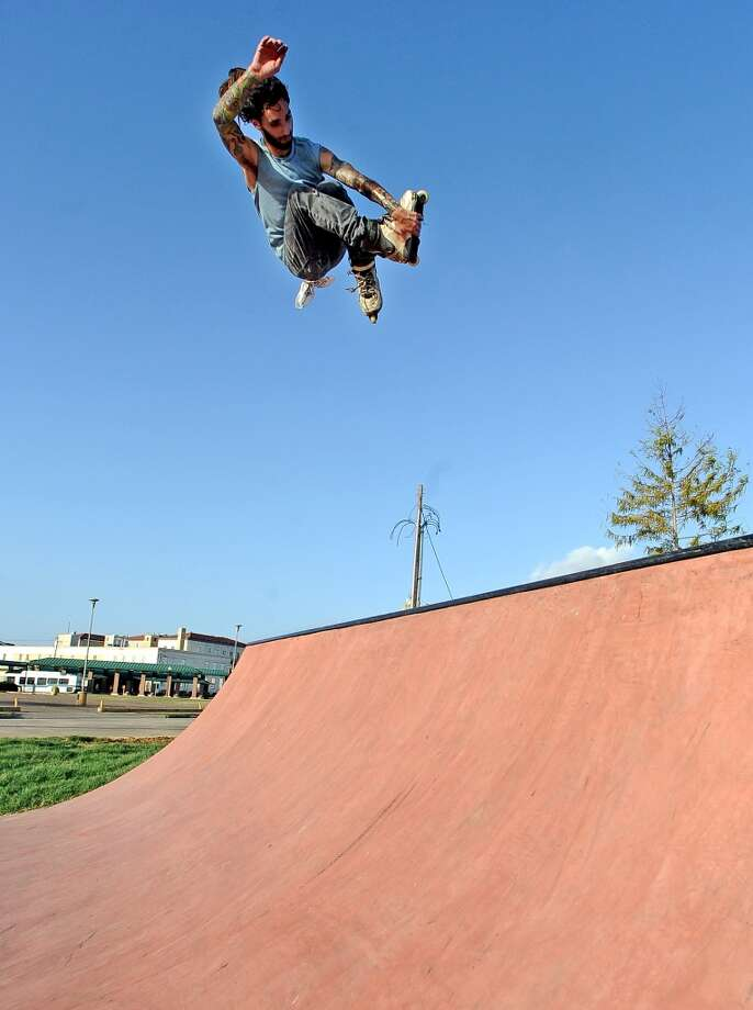 Simon Gonzales cross grabs an air out of the quarter-pipe on his rollerblades at the Beautiful Mountain Skate Plaza on Tuesday, August 6, 2013. Photo taken: Randy Edwards/The Enterprise Photo: Beaumont Enterprise