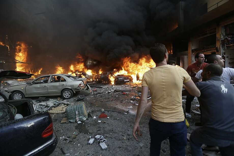 People gather after a powerful car blast hit a southern Beirut area that is a stronghold of Hezbollah, which has intervened on behalf of Syrian President Bashar Assad's government. Photo: Hussein Malla, Associated Press