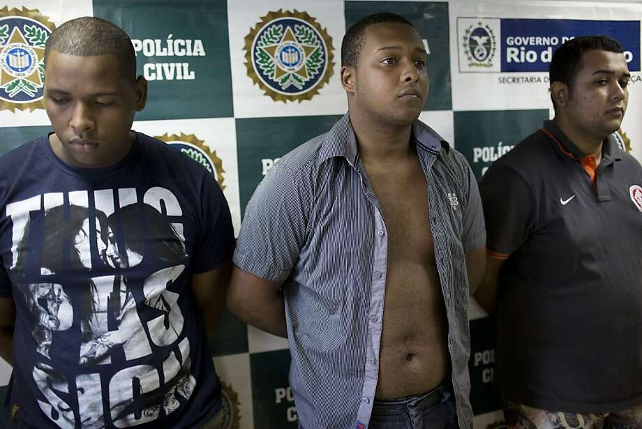 FILE - In this April 2, 2013 file photo, suspects Wallace Aparecido Souza Silva, left, Carlos Armando Costa dos Santos, center, and Jonathan Foudakis de Souza are presented to the press at the Special Police Unit for Tourism Support (DEAT) after their arrest in connection with an attack on tourists in Rio de Janeiro, Brazil. A court has convicted the three men in the gang rape of an American woman aboard a Rio de Janeiro public transit van. The court on Wednesday, Aug. 15, 2013 sentenced Jonathan Froudakis de Souza, 20, and Walace Aparecido de Souza Silva, 21, each to 49 years and three months in prison on rape, robbery and extortion charges. Carlos Armando Costa dos Santos was sentenced to 21 years and a minor has yet to be tried. (AP Photo/Felipe Dana, File) Photo: Felipe Dana, Associated Press