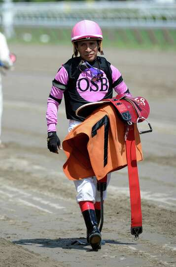 Jockey Edgar Prado carries his tack from the track after a race Wednesday, July 31, 2013 at Saratoga