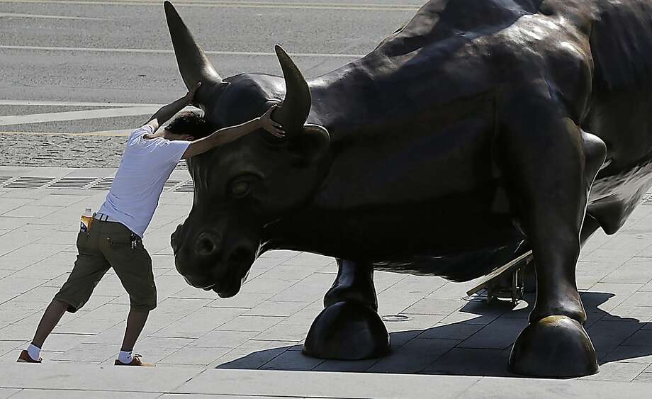 "A tourist takes the bull by the horns in Shanghai. The ""Charging Bull"" sculpture is by 