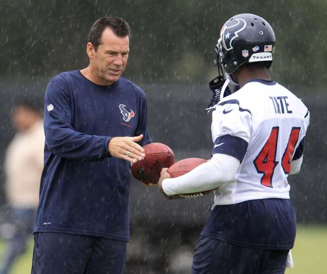 Head coach Gary Kubiak hands a football to running back Ben Tate in a light rain.