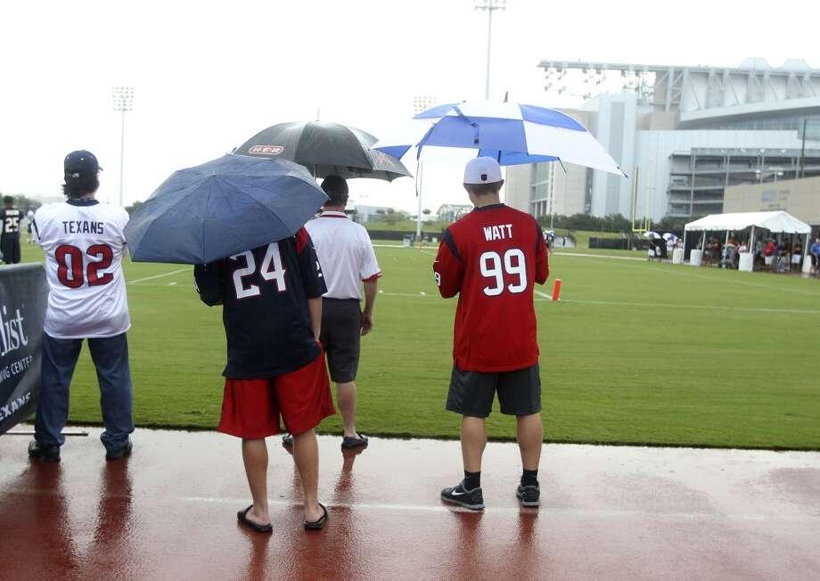 Fans watch practice from under umbrellas. Photo: Karen Warren, Chronicle