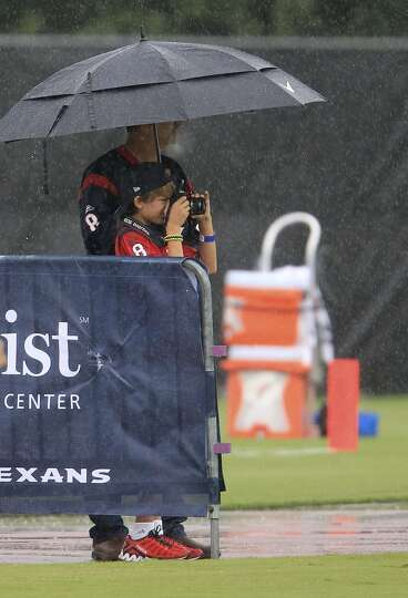 Fans watch practice from under an umbrella.