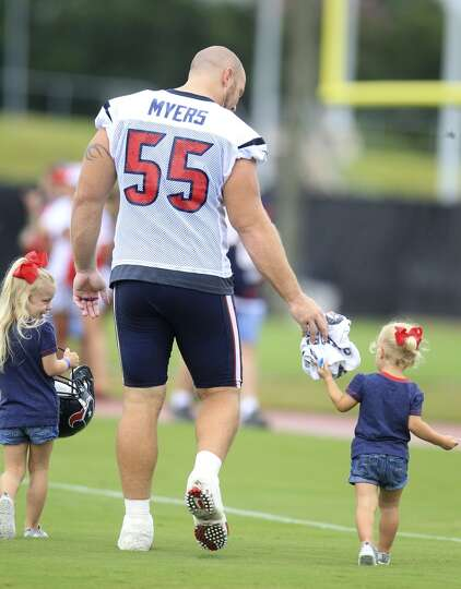 Center Chris Myers is surrounded by his daughters Makenna, 3, and Cailin, 20 months, after practice.