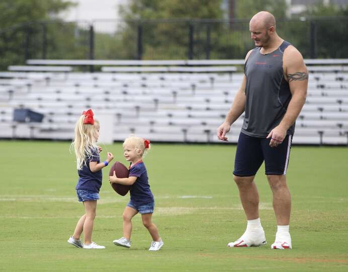 center Chris Myers plays with his daughters Makenna, 3, and Cailin, 20 months, after practice.