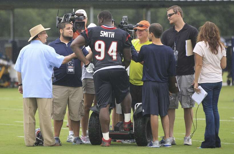 Texans defensive end Antonio Smith is surrounded by reporters after practice.