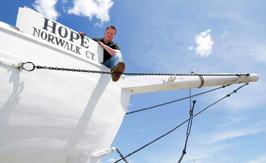 Shenton King, owner of The Hope, the last sail-powered oyster sloop built to sail the Long Island Sound, poses for a photo with the boat at Norwalk Cove Marina in Norwalk, Conn., on Thursday, August 15, 2013. Photo: Lindsay Perry / Stamford Advocate