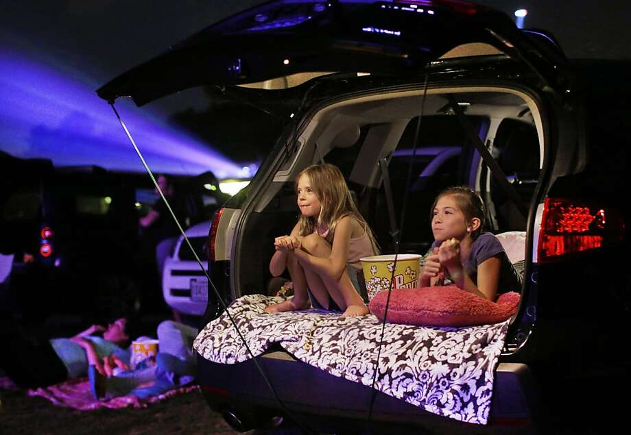 Going the way of buggy whips and newspapers: Maddie Essig (left), 10, watches a movie with her sister, Claire, 6, the way her grandparents used to - from the family car at a drive-in theater. Drive-ins like Bengies here in Middle River, Md., have been going out of business for years, but the film industry's conversion from 35mm film to digital prints could sound the death knell for the outdoor theaters because of the expense involved in revamping projectors for the digital age. Photo: Patrick Semansky, Associated Press