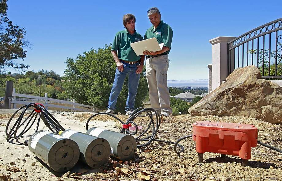 Coyn Criley (left) and Rufus Catchings of the U.S. Geological Survey are using seismographic sensors and recorders in the Hayward hills for Saturday's implosion. Photo: Michael Macor, San Francisco Chronicle