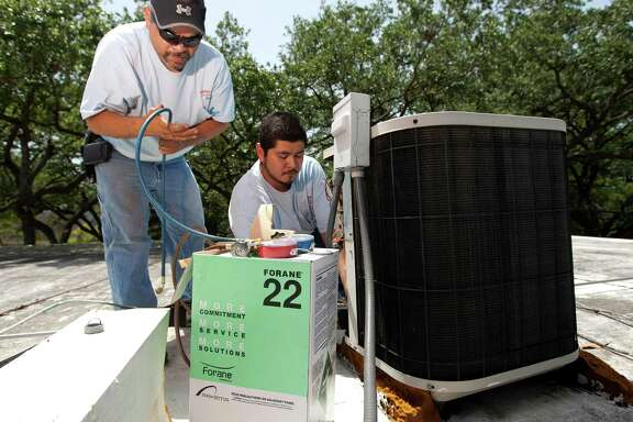 Stuffy Martinez, left, and Ernie Morales work on an air-conditioning unit. Martinez says perspiring causes him to lose 15 to 20 pounds every summer, but he gains it back in the off-season.