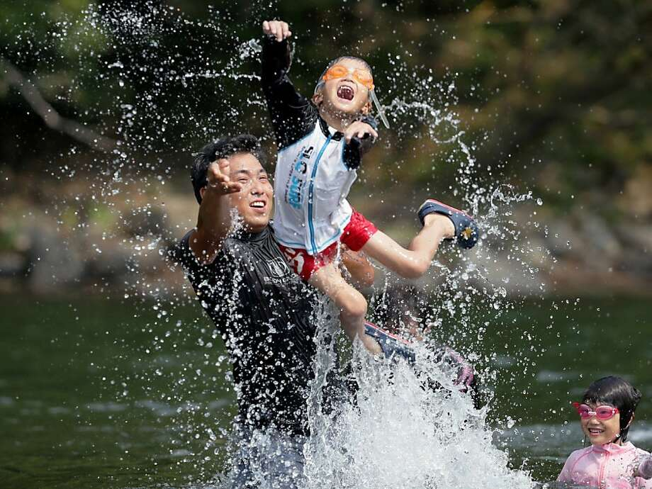 Rising temperatures in the Land of the Rising Sun: A family plays in the river in Shimanto, Japan, which on Monday set a record temperature of 41 degrees Celsius. Photo: Jiji Press, AFP/Getty Images