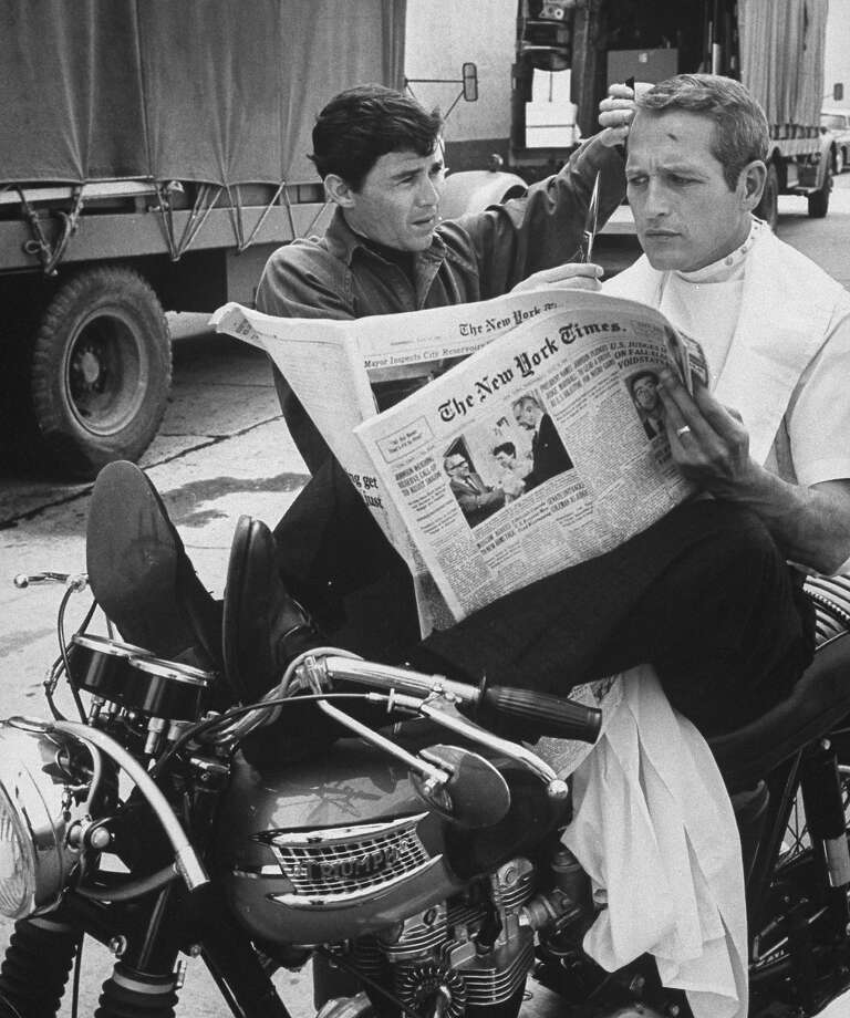 Paul Newman gets a trim while relaxing on some classic British iron. Photo: Don Cravens, Time & Life Pictures/Getty Image / Don Cravens