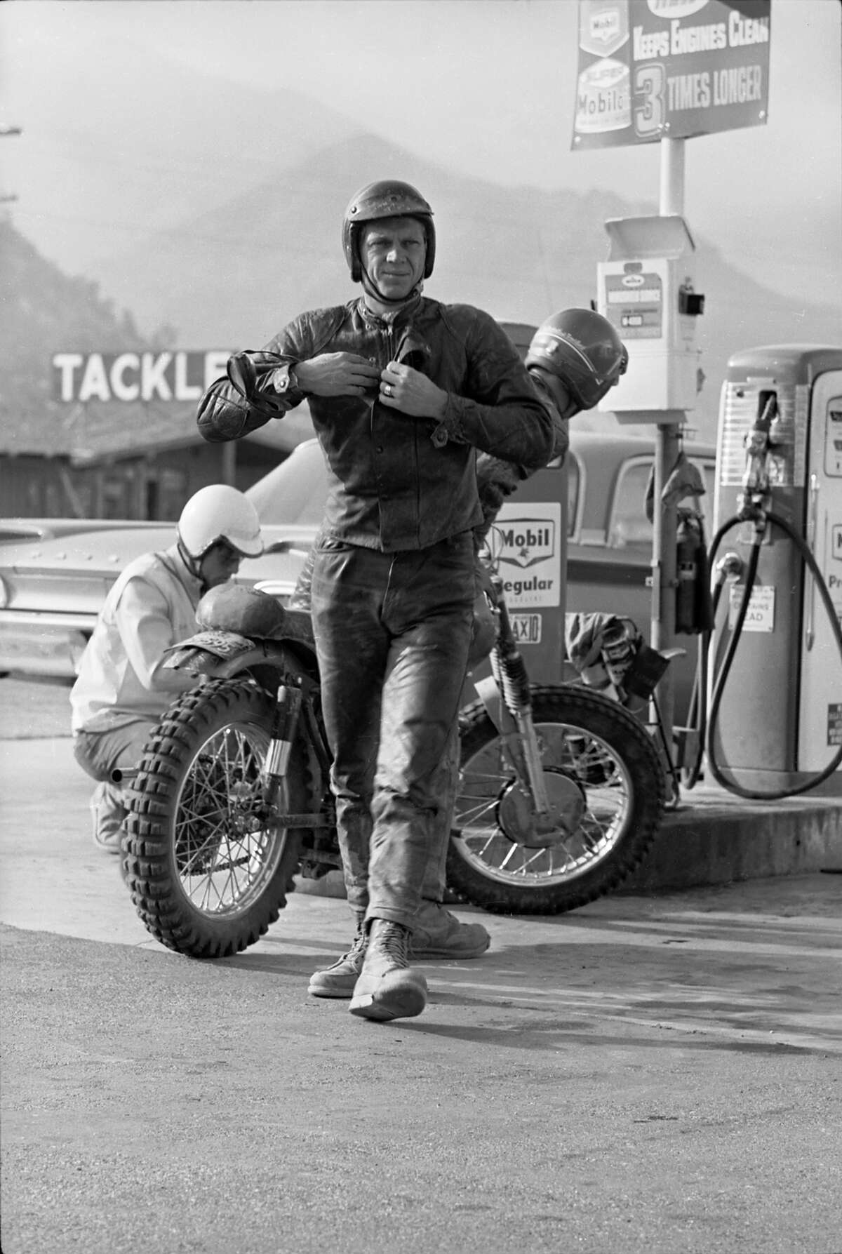 Steve McQueen stops at a gas station to refuel his motorcycle during a 500 mile race across the Majove Desert.