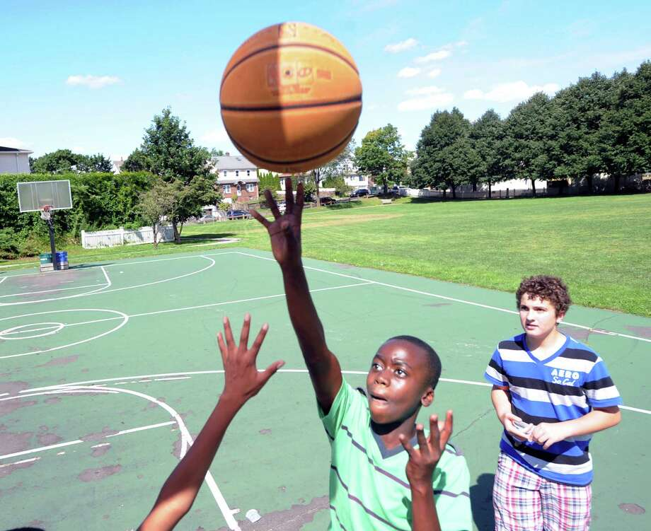 At left, Mehki Williams, 13, of Greenwich, scores on a layup after getting past Joey Frangione, also 13, also of Greenwich, during a basketball game of Twenty-one at the Hamilton Avenue School court in Chickahominy, Thursday, August 15, 2013. Photo: Bob Luckey / Greenwich Time