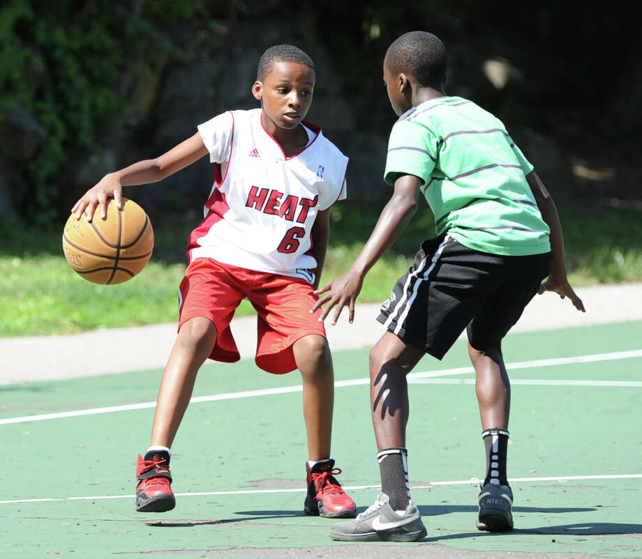 At left, Don Lowe, 13, of Greenwich, prepares to dribble behind his back while being defended by Mehki Williams, also 13, also of Greenwich, during a basketball game of Twenty-one at the Hamilton Avenue School court in Chickahominy, Thursday, August 15, 2013. Photo: Bob Luckey / Greenwich Time