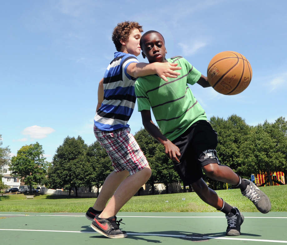 At right, Mehki Williams, 13, of Greenwich, drives the baseline while being defended by Joey Frangione, also 13, also of Greenwich, during a basketball game of Twenty-one at the Hamilton Avenue School court in Chickahominy, Thursday, August 15, 2013. Photo: Bob Luckey / Greenwich Time