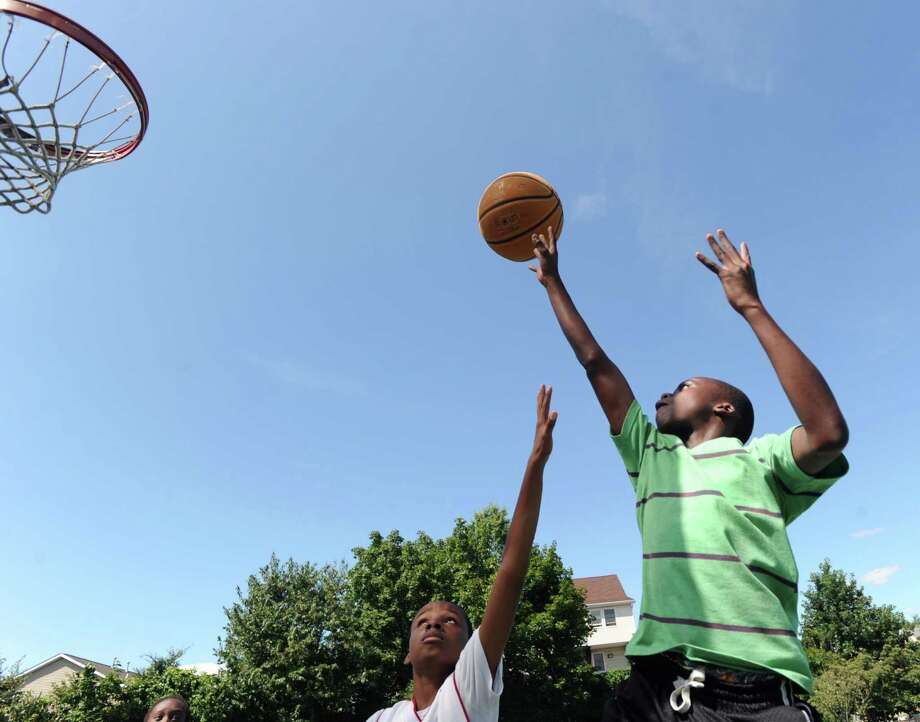 At right, Mehki Williams, 13, of Greenwich, gets off a shot while being defended by Don Lowe, also 13, also of Greenwich, during a basketball game of Twenty-one at the Hamilton Avenue School court in Chickahominy, Thursday, August 15, 2013. Photo: Bob Luckey / Greenwich Time