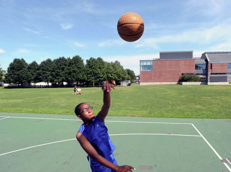 Isaiah Roberts, 13, of Greenwich, takes a running lefty hook shot in the lane during a basketball game of Twenty-one at the Hamilton Avenue School court in Chickahominy, Thursday, August 15, 2013. Photo: Bob Luckey / Greenwich Time