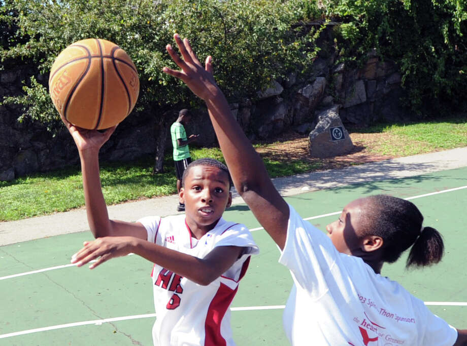 At left, Don Lowe, 13, of Greenwich, shoots over Saquoiya Bennett, 15, also of Greenwich, during a basketball game of Twenty-one at the Hamilton Avenue School court in Chickahominy, Thursday, August 15, 2013. Photo: Bob Luckey / Greenwich Time