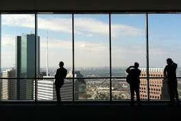 People look out the windows of the JPMorgan Chase Tower's 60th floor observation deck Wednesday, Jan. 23, 2013, in Houston. ( James Nielsen / Chronicle )