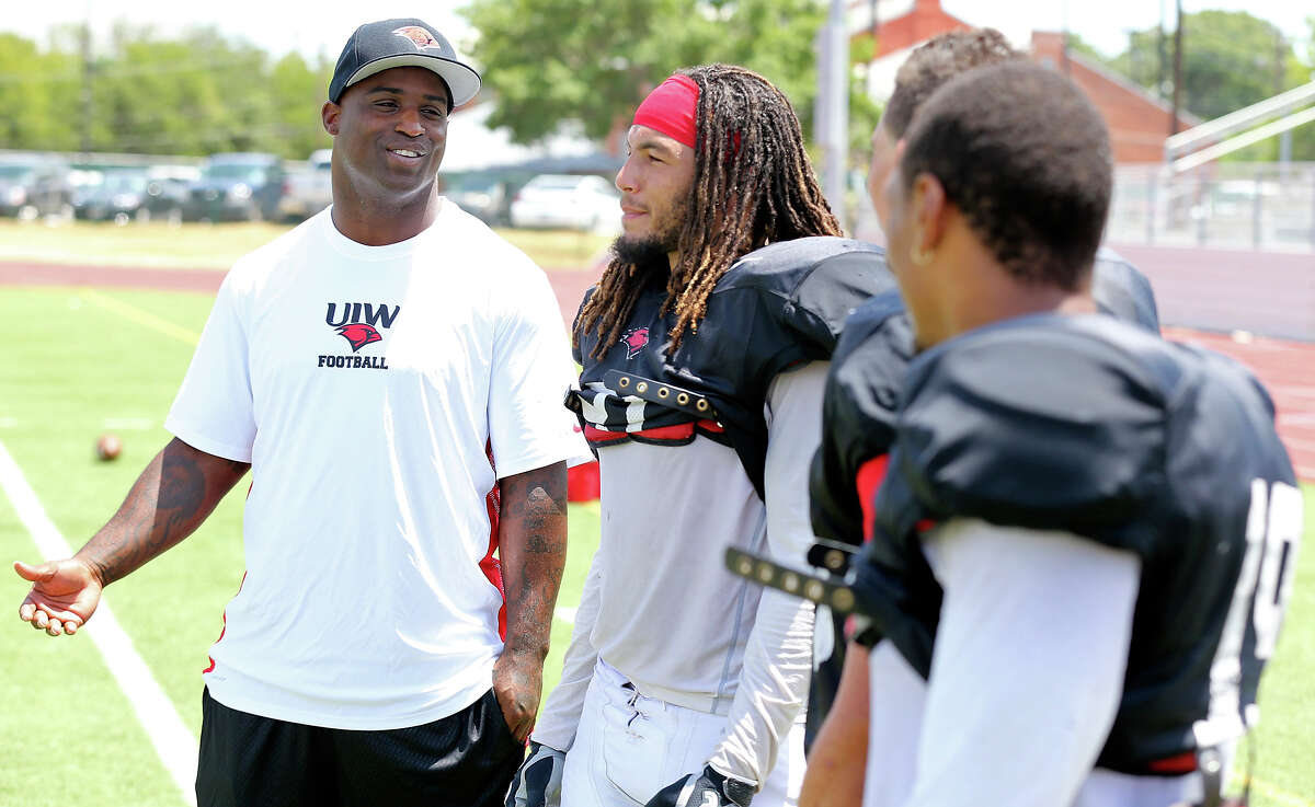 University of the Incarnate Word new assistant football coach Ricky Williams (left) talks with player Devin Haywood and others during practice held Thursday Aug. 15, 2013 at the university.