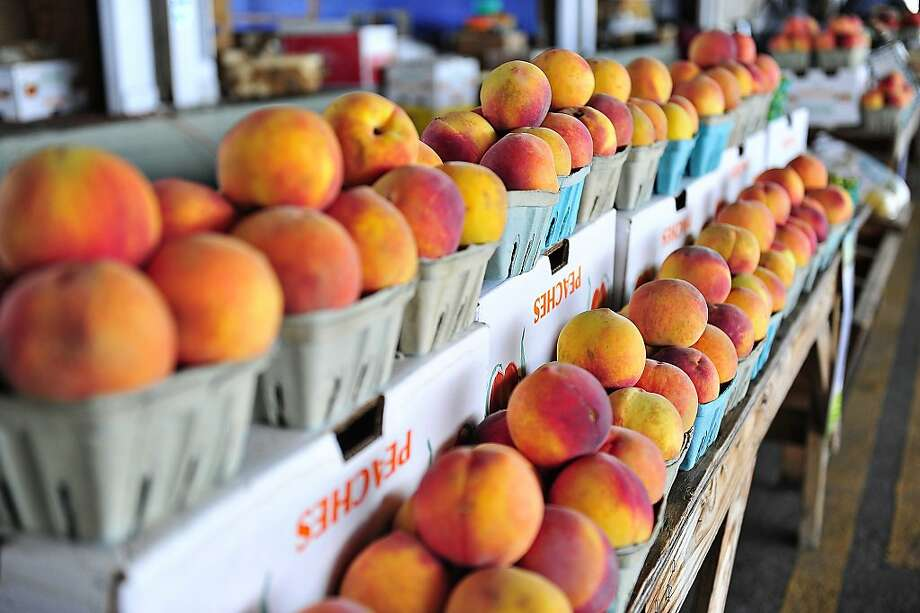 FOR USE MONDAY, AUG. 12 AND THEREAFTER - In this Aug. 2, 2013 photo, baskets of peaches are displayed at Mattie Judge's' booth at the Augusta Farmers Market in Augusta, Ga. (AP Photo/The Augusta Chronicle, Jon-Michael Sullivan) Photo: Jon-Michael Sullivan, Associated Press