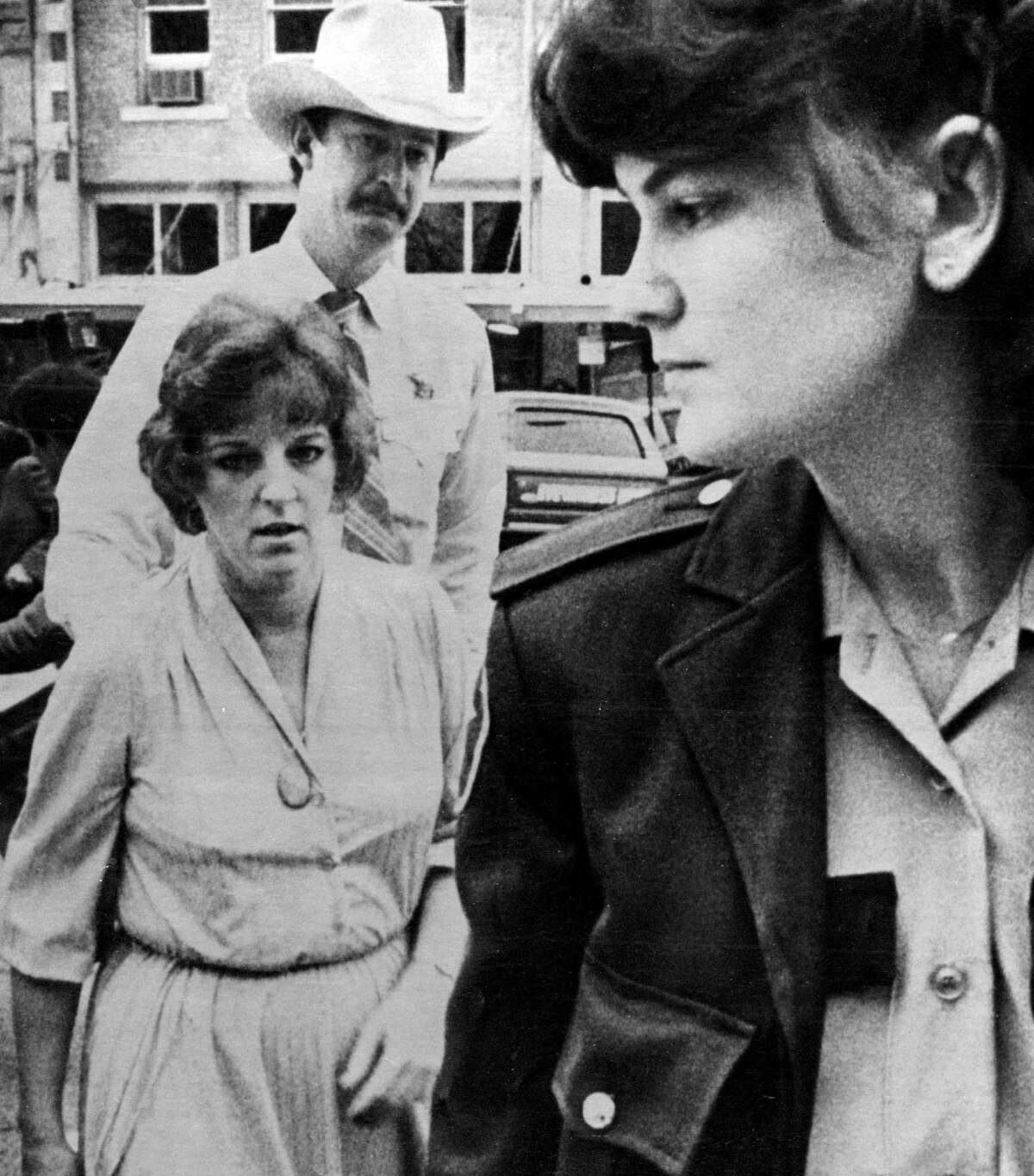 1/16/1984 Georgetown, Texas Genene Jones, 33, facing trial on a murder charge alleging she killed a 15-month -old girl with a dose of a paralyzing drug arrives at Williamson County(Texas) courthouse Monday for the start of her trial. Escorting Ms. Jones are Deputies Monica Kiepac and Jim WIlson.