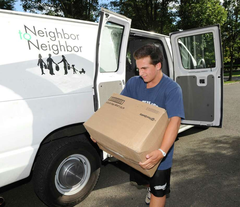 Marco Pastore, 15, of Greenwich, a Neighbor to Neighbor volunteer, carries one of the boxes containing 150 bed sheets that the Nathaniel Witherell nursing home donated to the Neighbor to Neighbor organization in Greenwich, Thursday, August 15, 2013. The donation of the sheets was facilitated by the Needs Clearing House organization that was started by Greenwich resident Joe Kaliko and Republican state Rep. Fred Camillo. Their organization acts as a resource and a bridge for individuals and businesses that want to give back to the community. Neighbor to Neighbor is a community service organization that distributes clothes, food and other necessities to those in need. Photo: Bob Luckey / Greenwich Time