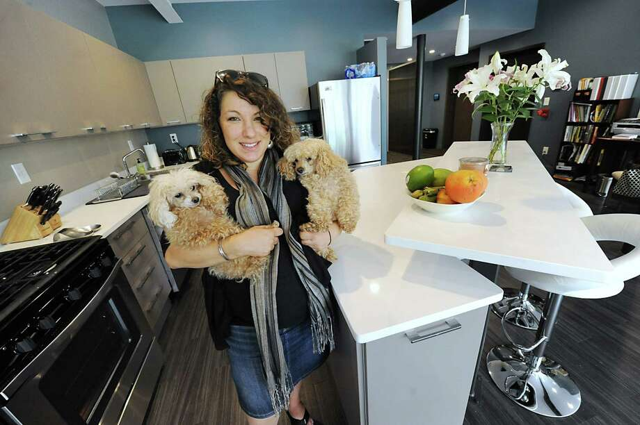 Ashley Rondini, who is expecting a baby, holds her dogs Dolche and Vita while standing in the kitchen of the apartment which she shares with her husband Thursday, Aug. 15, 2013, at Liberty Lofts on Broadway  in Albany, N.Y.  (Lori Van Buren / Times Union) Photo: Lori Van Buren / 00023522A