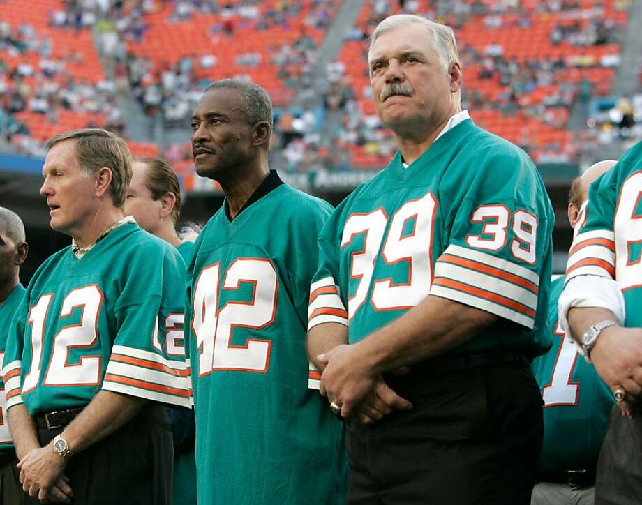 Miami Dolphins players from the 1972 unbeaten team, quarterback Bob Griese (12), wide receiver Paul Warfield (42) and running back Larry Csonka (39) stand during a ceremony honoring the team at a football game against the Baltimore Ravens at Dolphin Stadium in Miami Sunday, Dec. 16, 2007. (AP Photo/Lynne Sladky) Photo: Lynne Sladky, AP