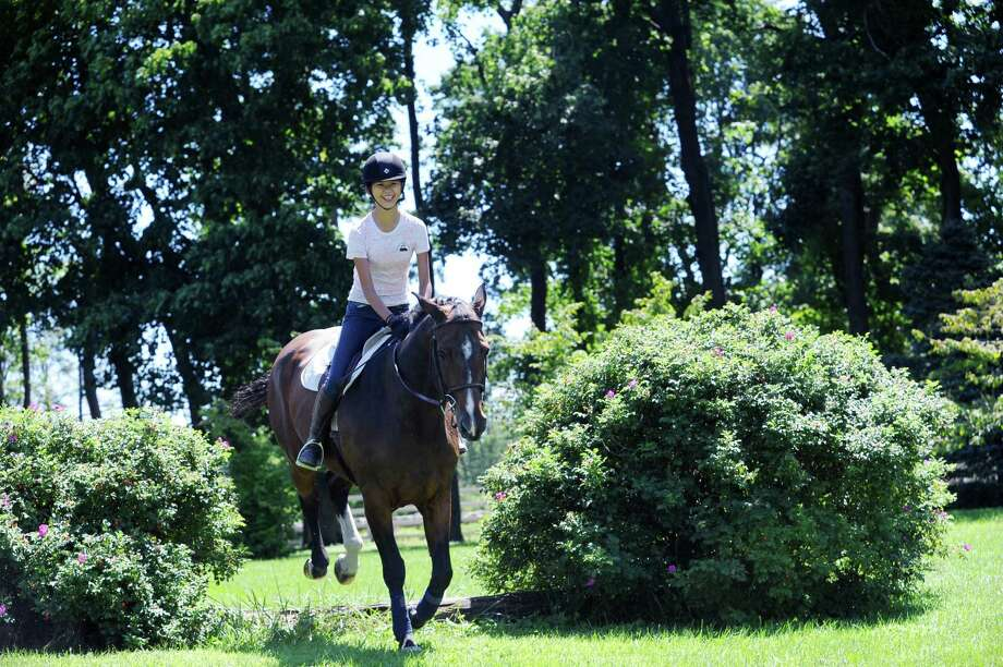 Ariana Swei, 13, of Greenwich, rides a pony at Country Lane Farm's Round Hill Barn, in Greenwich, Conn., Wednesday, August 14, 2013. Photo: Helen Neafsey / Greenwich Time