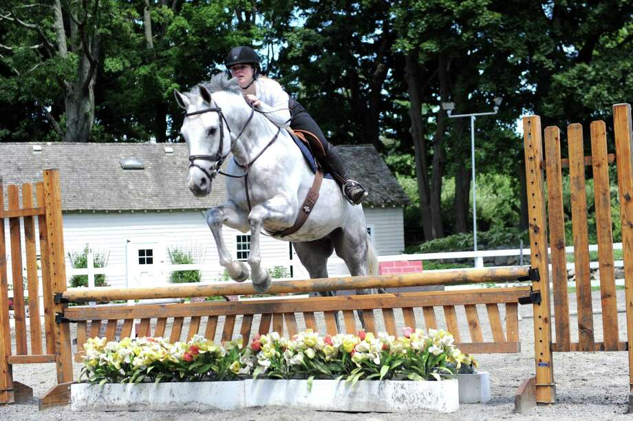 Lindsay Schauder, 13, jumps a horse, at Country Lane Farm's Round Hill Barn, in Greenwich, Conn., Wednesday, August 14, 2013. Photo: Helen Neafsey / Greenwich Time