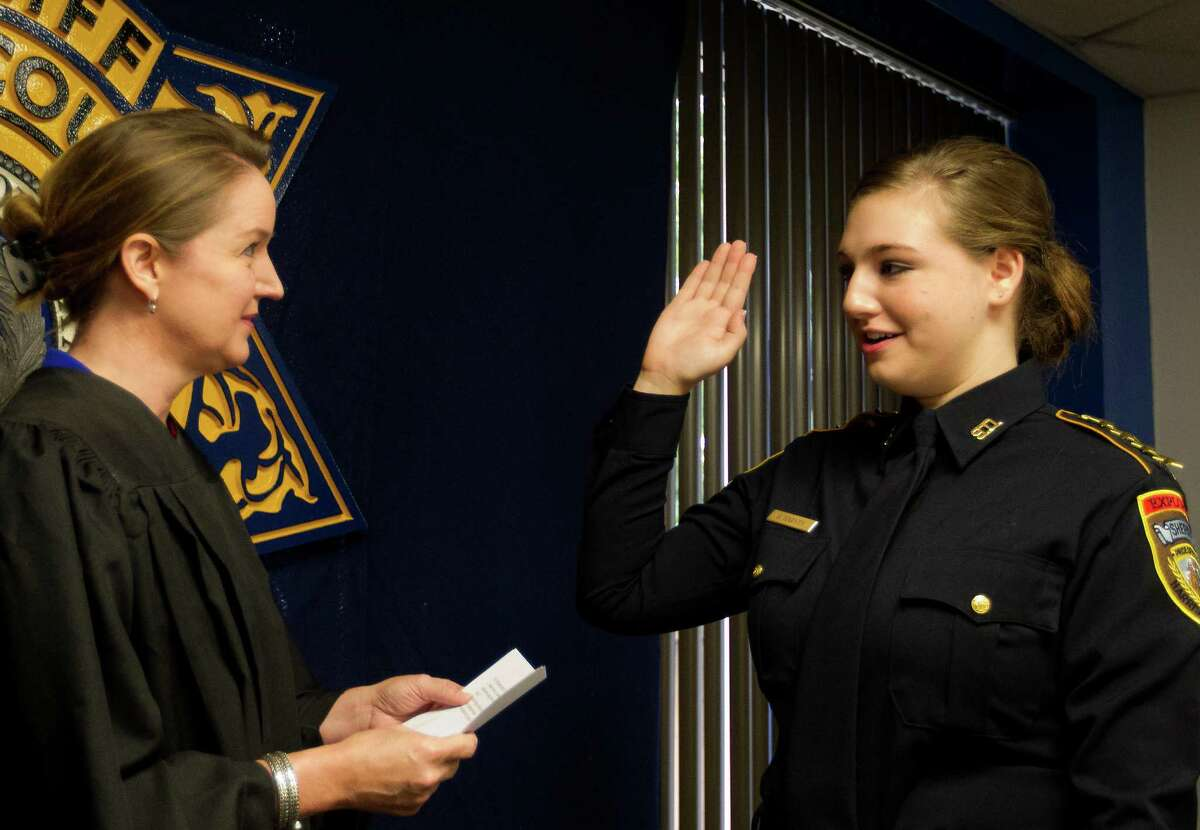 Harris County District Court Judge Katherine Cabaniss, left, swears in Harris County Sheriff's Office Explorer, Sergeant Haley Rose Harvey, right, in the 701 N. San Jacinto Street Jail's officer dining room, Thursday, Aug. 15, 2013, in Houston. The Concordia Lutheran High School junior took the oath to become the first annual Harris County