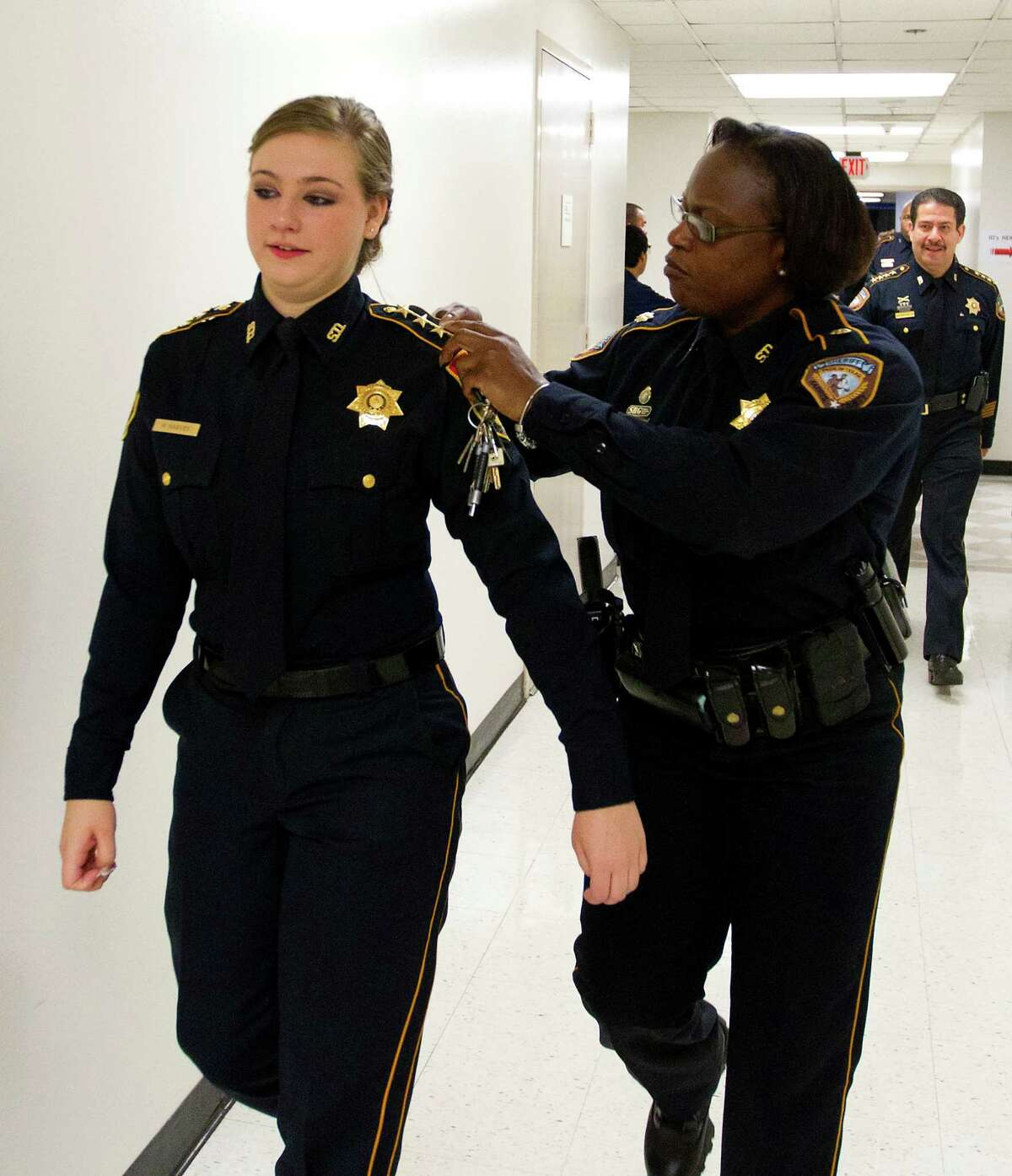 Harris County Sheriff's Department Master Peace Officer, S. C. Jones, adjusts the stars of Harris County Sheriff's Office Explorer, Sergeant Haley Rose Harvey, as she's trailed by Sheriff Adrian Garcia in the 701 N. San Jacinto Street Jail's officer dining room, Thursday, Aug. 15, 2013, in Houston. The Concordia Lutheran High School junior took the oath to become the first annual Harris County