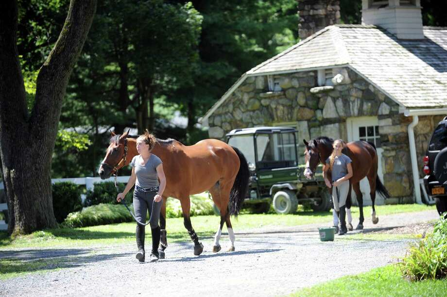 Abby Bartley, left, an instructor, with a brown horse, and Sloan Jocoby,13, with a horse at Country Lane Farm's Round Hill Barn, in Greenwich, Conn., Wednesday, August 14, 2013. Photo: Helen Neafsey / Greenwich Time