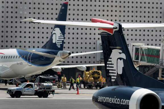 Grupo Aeromexico SAB airplanes sit on the tarmac at Benito Juarez International Airport (AICM) in Mexico City, Mexico, on Monday, Aug. 5, 2013. Grupo Aeromexico SAB, Mexico's largest airline, is preparing to tap the U.S. corporate bond market to help pay for an $11 billion Boeing Co. jet order that marks the country's biggest aircraft purchase ever. Photographer: Susana Gonzalez/Bloomberg