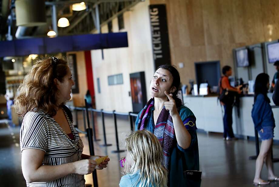 Jericha Senyak (cq), right, helps a visitor to the Exploratorium in San Francisco, Calif., Thursday, August 15, 2013.  The Exploratorium is laying off some of its employees because of lower attendance than expected. Photo: Sarah Rice, Special To The Chronicle