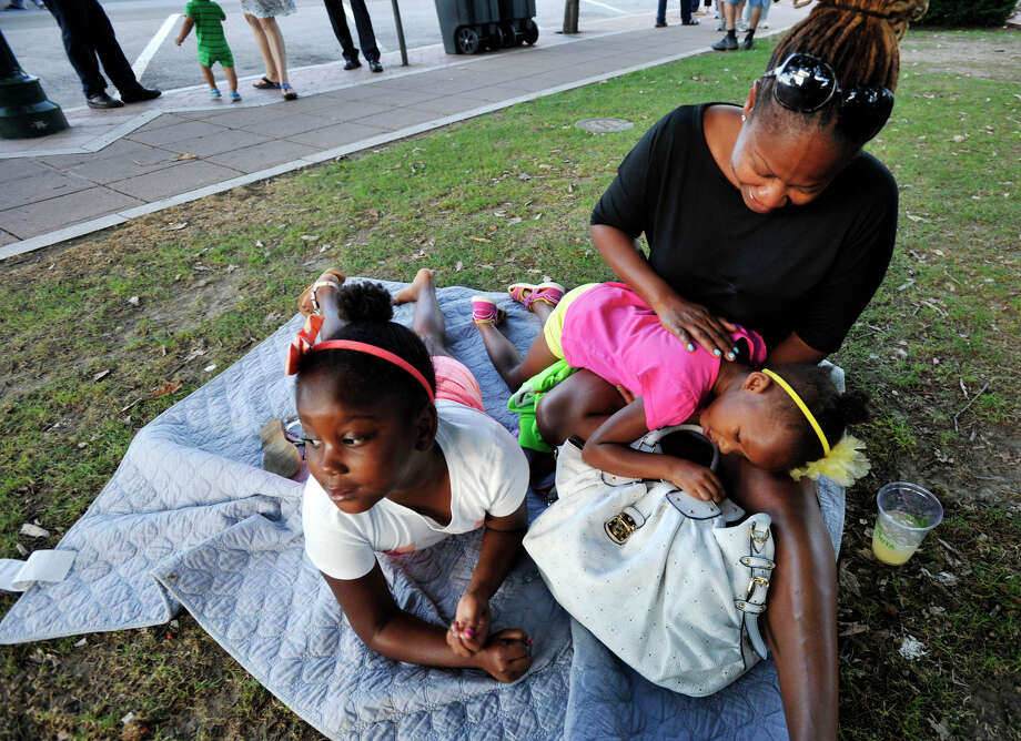 Taylor Dunbar lays on the lap of her mother, Denise, as her sister Raegan looks on during the Alive@Five concert series at Columbus Park in Stamford on Thursday, Aug. 15, 2013. Hearst Connecticut Newspapers are one of the sponsors of the event. Photo: Jason Rearick / Stamford Advocate