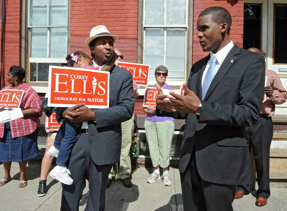 Mark Robinson, left, who is running for Common Council as a Democrat in the 5th Ward, joins Albany mayoral candidate Corey Ellis as he discusses his plans to provide tax incentives for homeowners to revitalize abandoned and vacant buildings and units throughout the city on Thursday, Aug. 15, 2013 in Albany, N.Y. T(Lori Van Buren / Times Union) Photo: Lori Van Buren / 00023515A